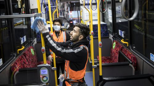 Workers clean a bus in Sydney to prevent the spread of COVID-19.