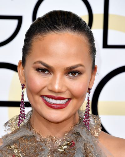 <p>Chrissy Teigen rocked a true red lipstick and the sexiest of bronzed eyes. Hair was sleek and chic - a hot trend on the day.</p> <p>Image: Getty.</p>