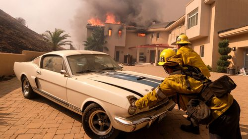 Firefighters push a vehicle from a garage as the Woolsey fire burning a home near Malibu .