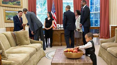 A young boy sorts through a bowl of apples as President Obama greets a visitor. (Flickr/White House)