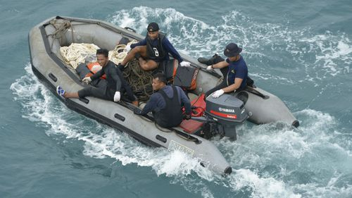 Indonesian navy divers arrive on boats after conducting operations to lift the tail of AirAsia Flight 8501. (AAP)