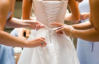 Bridesmaids doing up bride wedding dress