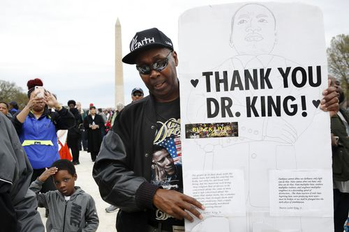 Leonard Patterson, of  Virginia, holds a handmade sign thanking Martin Luther King Jr., while attending the A.C.T. To End Racism rally in Washington. (AAP)