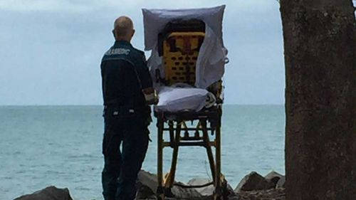 The paramedic taking the patient to see the ocean. (Facebook/Queensland Ambulance)