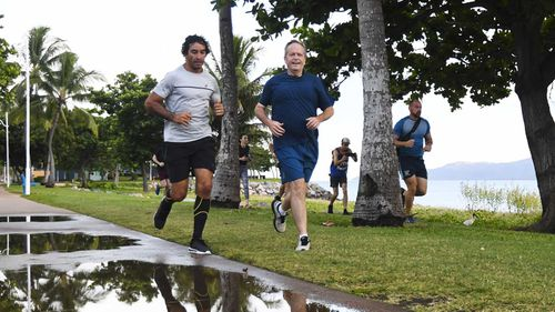 Bill Shorten goes for his morning jog in Townsville with NRL legend Johnathan Thurston.