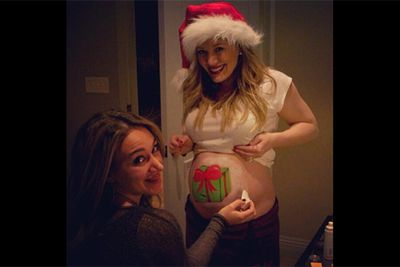 Who needs a blank canvas when you've got a big ol' belly to paint? Hilary Duff and sister, Haylie, got into the Christmas spirit with this creative body-painting snap.<br/><br/>Image: Twitter @hilaryduff