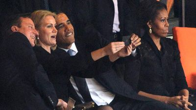 Barack Obama, David Cameron and Helle Thorning-Schmidt share a light moment among a sombre crowd dressed in black.