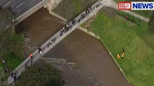 Rescuers search a creek near Dandenong for a young boy swept away. (9NEWS)