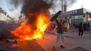 A protester shouts in front of a fire during a protest in Los Angeles