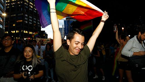 Supporters of same-sex marriage are seen celebrating the victory of the 'Yes' vote in the marriage equality survey at a street party. (AAP)
