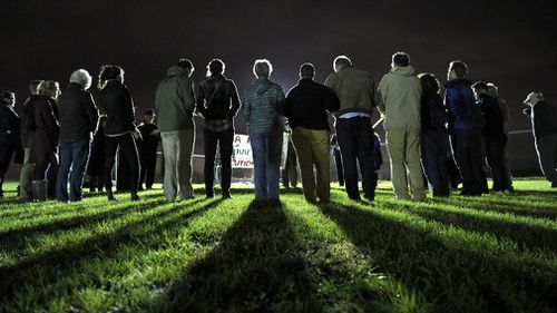 People form a circle and pray against the death penalty.