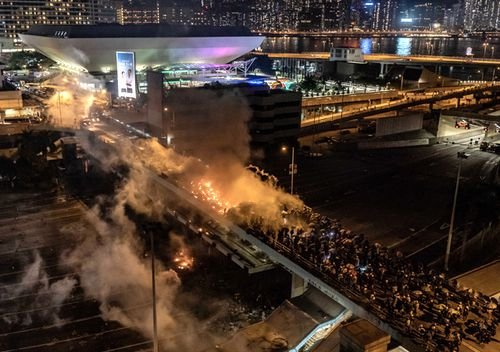 "Protesters and police clash as on a bridge at The Hong Kong Polytechnic University. Anti-government protesters organised a general strike as demonstrations in Hong Kong stretched into its sixth month with demands for an independent inquiry into police brutality, the retraction of the word ""riot"" to describe the rallies, and genuine universal suffrage"