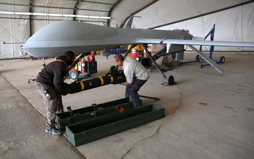 Contract workers load a Hellfire missile onto a US Air Force MQ-1B Predator unmanned aerial vehicle (UAV), at a secret air base in the Persian Gulf region. The US military and coalition forces use the base, located in an undisclosed location, to launch drone airstrikes against Islamic State in Iraq and Syria.