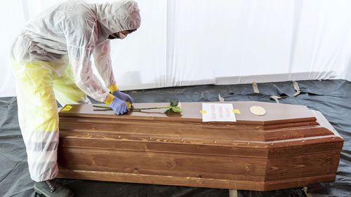 A flower is placed on the coffin of a COVID-19 victim in Italy, one of the countries hardest hit by the pandemic.
