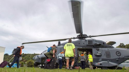 People walk to a helicopter with their suitcases as hundreds of tourists are evacuated from Kaikoura. (AFP / New Zealand Defence Force)