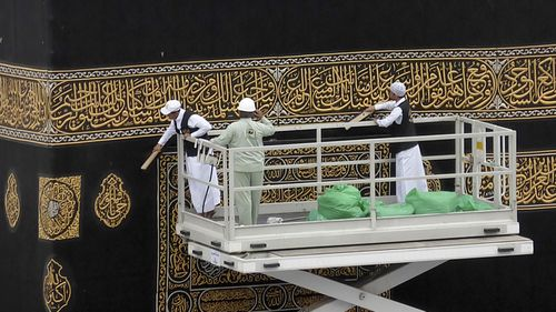 Workers clean the Kiswah, the cloth that covers the Kaaba, the cubic building toward which Muslim believers turn when praying, at the Grand Mosque, in Mecca, Saudi Arabia, Monday, Feb. 24, 2020.