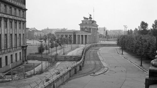 11/23/1962-West Berlin, Germany- The Communist Wall in Berlin winds its way through the heart of the city against the background of the Brandenberg Gate in the British sector. Built during the night more than a year ago, the Wall is topped by barbed-wire barricades and extends some 22 miles across busy streets and canals, through quiet neighborhoods and garden plots.