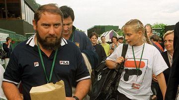 Australia's Jelena Dokic walks through Wimbledon with her father, Damir, on June 22, 1999, after defeating Martina Hingis in their Women's Singles, first round match. (AAP)