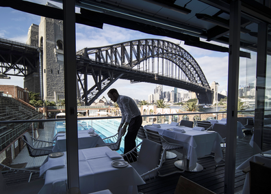 Iain Wood, assistant manager at Aqua Dining, sets tables before opening to guests on May 16, 2020 in Sydney, Australia.