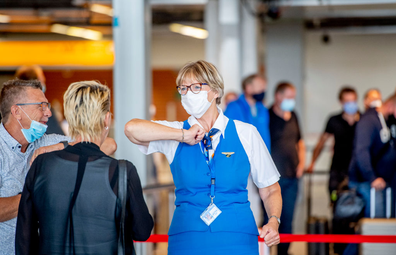 A KLM staff doing the elbow bump with travellers while wearing a face mask
