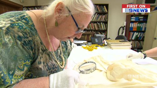 Costume historian Kay Inverarity inspected Mr Pike's royal find. (9NEWS)
