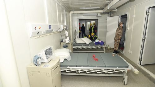 A Chinese army medic looks at a patient room at the Huoshenshan temporary field hospital.