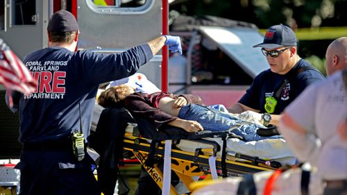Medical personnel tend to a victim outside of Stoneman Douglas High School in Parkland.