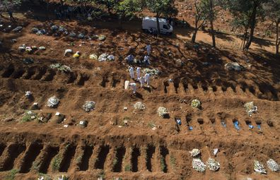 Cemetery workers in protective clothing bury a person who died of COVID-19, at the Vila Formosa cemetery in Sao Paulo, Brazil.