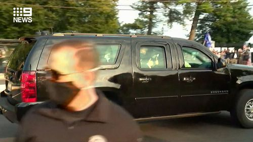 US President Donald Trump briefly left the hospital in his car to wave to supporters gathered outside.