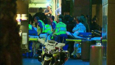 Paramedics run to the entrance of the cafe to take the injured to safety. (9NEWS)