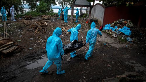 Health workers wearing personal protective equipment carry the body of a COVID-19 victim for cremation.