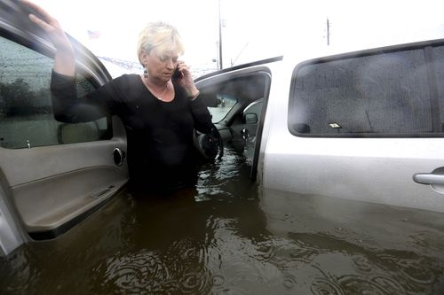 Rhonda Worthington talks on her cell phone with a 911 dispatcher after her car became stuck in rising floodwaters. (AP)