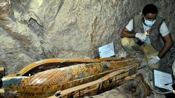 Experts inspect the sarcophagus which were found with mummies and sculptures inside a grave during archaeological works at Dra' Abu el-Naga' region in Luxor, Egypt on April 18, 2017. (AFP)