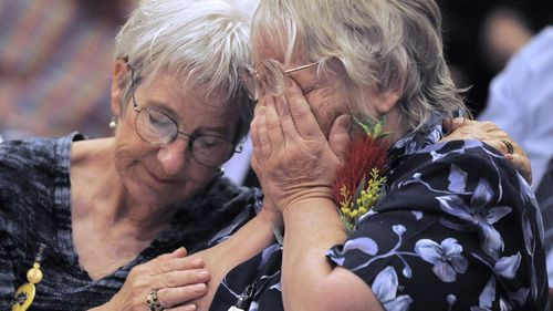 Two women comfort each other as they attend a ceremony in the Australian capital of Canberra, Monday, Nov. 16, 2009, where Australian Prime Minister Kevin Rudd issued an apology to thousands of impoverished British children shipped to Australia