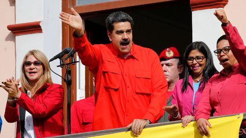 Venezuela's President Nicolas Maduro, centre, addresses leftist red shirt supporters on the balcony of the presidential palace.