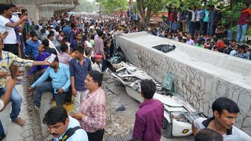 People crowd around the site of an accident where a section of an under construction overpass collapsed in Varanasi, India. (AAP)