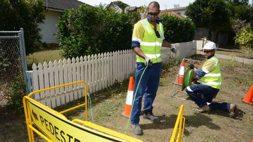 Workers installing a fibre optic cable as part of the National Broadband Network rollout. (AAP)