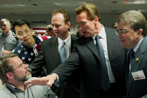 A file photo showing the then California Governor Arnold Arnold Schwarzenegger congratulate NASA staff after the rover's Mars landing in January 2004