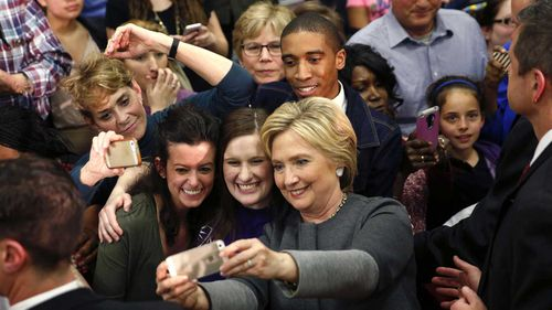 Hillary Clinton snaps a selfie with supporters in Virginia. (AAP)