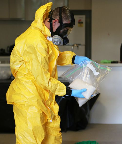 A forensic officer wearing a full containment suit, including mask, handles some drugs. (Supplied)