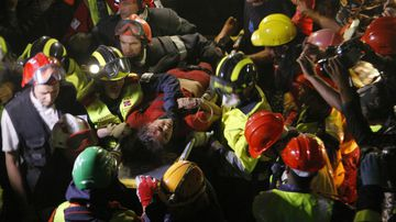 Krishna Devi Khadka is carried on a stretcher after being rescued from a building that collapsed in Kathmandu. (AAP)