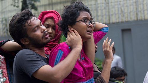 People assist an injured student as Dhaka University students protesters gather during the eight-day protest demanding safer roads.