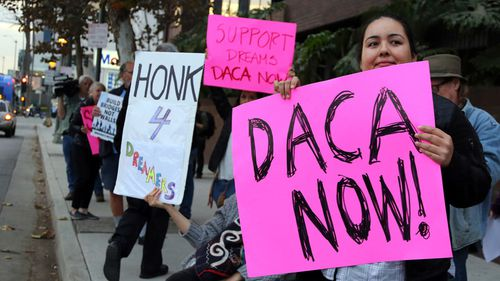 Demonstrators urging the Democratic Party to protect the Deferred Action for Childhood Arrivals Act (DACA) rally outside the office of California Democratic Senator Dianne Feinstein in Los Angeles on January 3, 2018. (AAP)