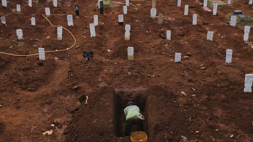 A municipal cemetery worker digs a grave in a special cemetery for suspected Covid-19 Coronavirus victim on September 11, 2020 in Jakarta, Indonesia.