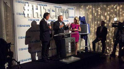 Hitchener gives a speech alongside reporters Tony Jones and Livinia Nixon. (9NEWS)