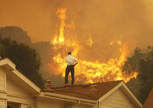 A man on a rooftop looks at approaching flames as the Springs fire continues to grow in 2013, near Camarillo, California.