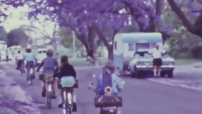 In one shot a group of children are seen riding their bikes as the man poses next to his caravan.