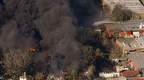 Black plumes of smoke rise from an out-of-control blaze near Penrith, in Sydney's West. (9NEWS)