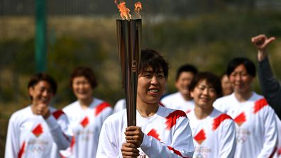 Azusa Iwashimizu (L), member of Japan women's football national team, lights the torch from the celebration cauldron during the Tokyo 2020 Olympic Torch Relay Grand Start. (Getty)