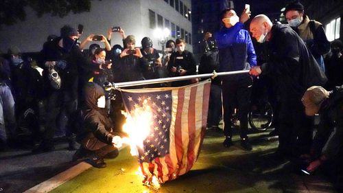 A protester lights an American flag on fire during a demonstration in Portland, Oregon.